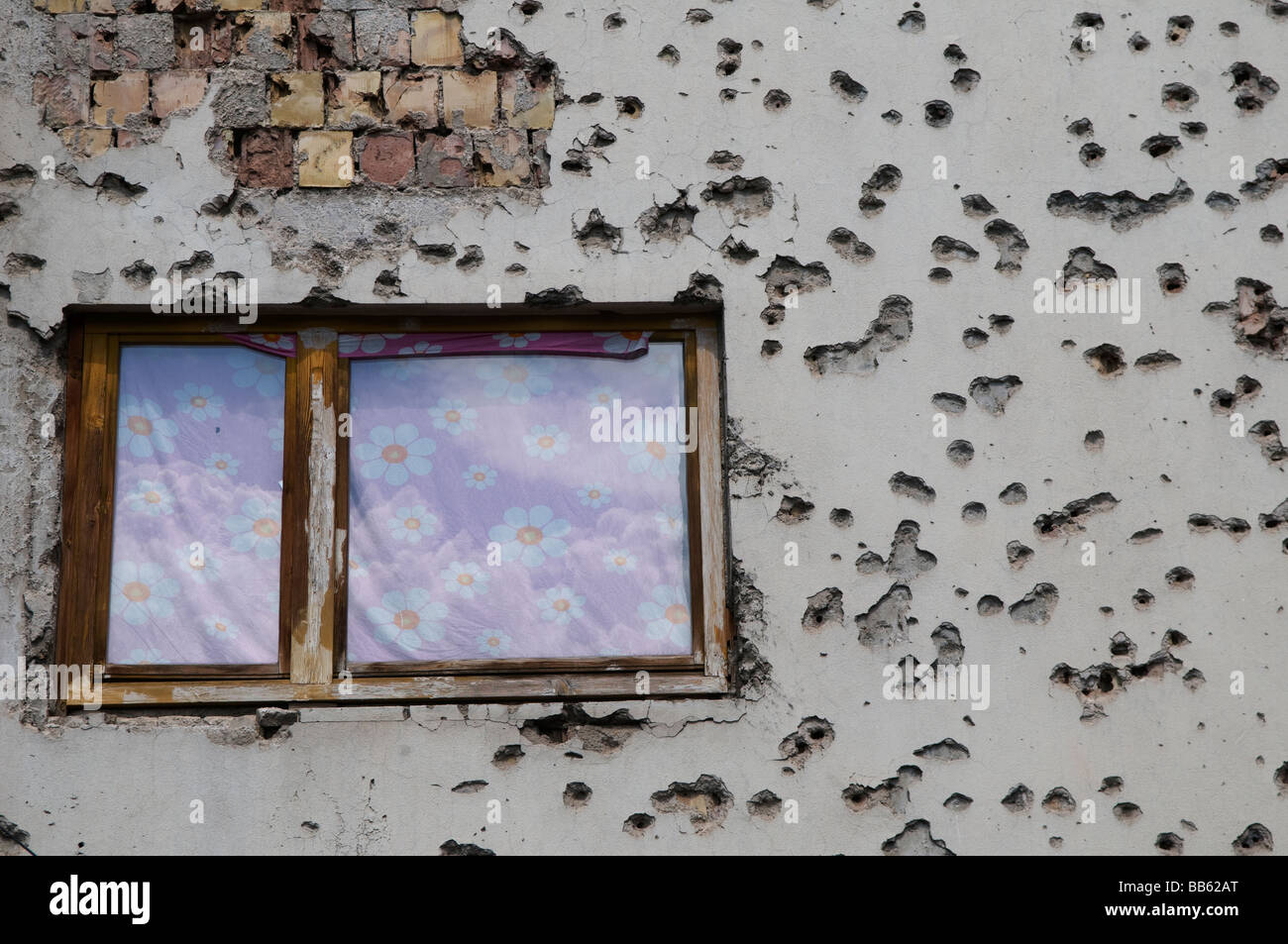 Facade of a house is riddled with bullet holes from the 1992-95 war in downtown Sarajevo, Bosnia Herzegovina - Stock Image