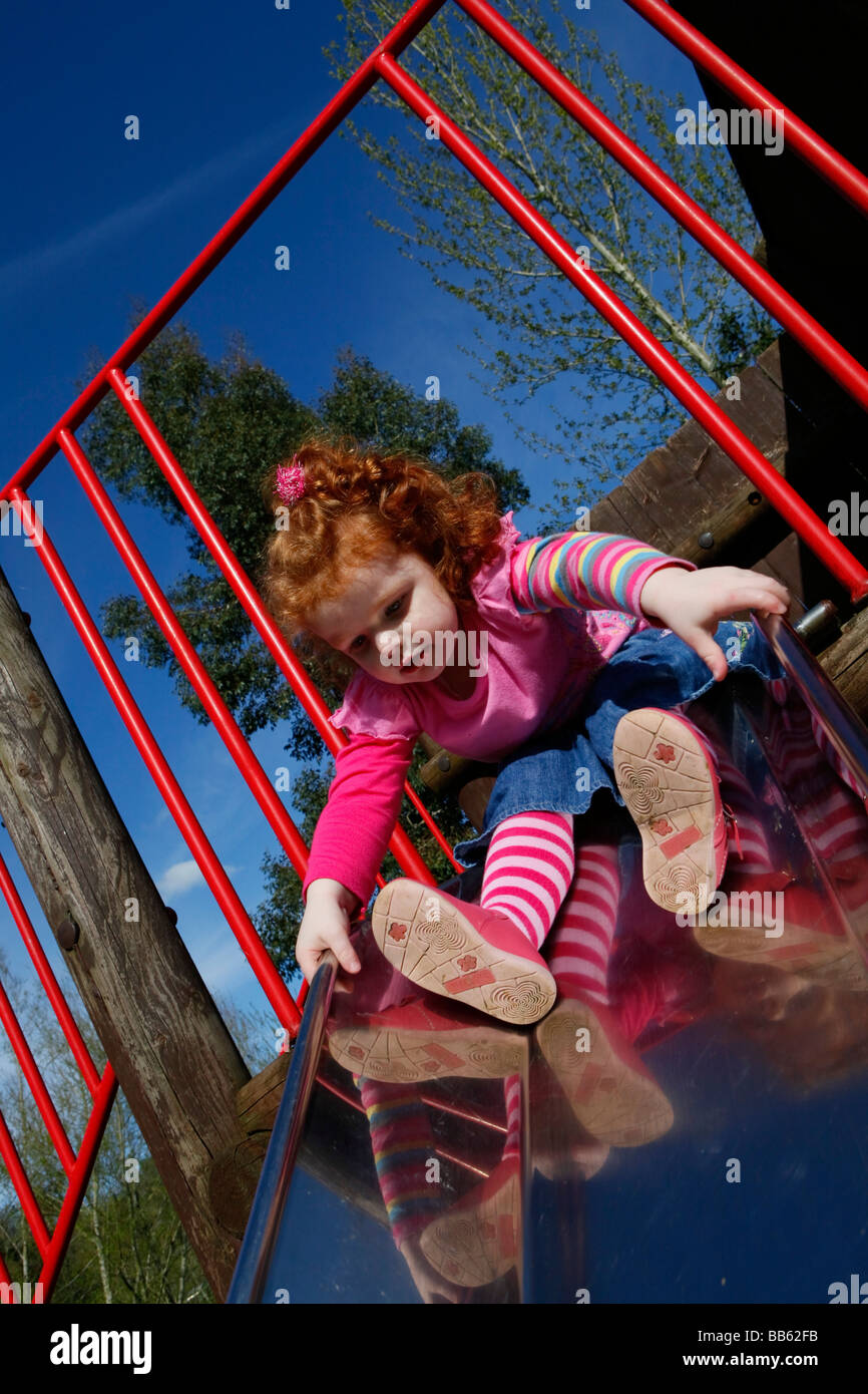 Little girl with red hair playing on the slide in the park on a sunny day. - Stock Image