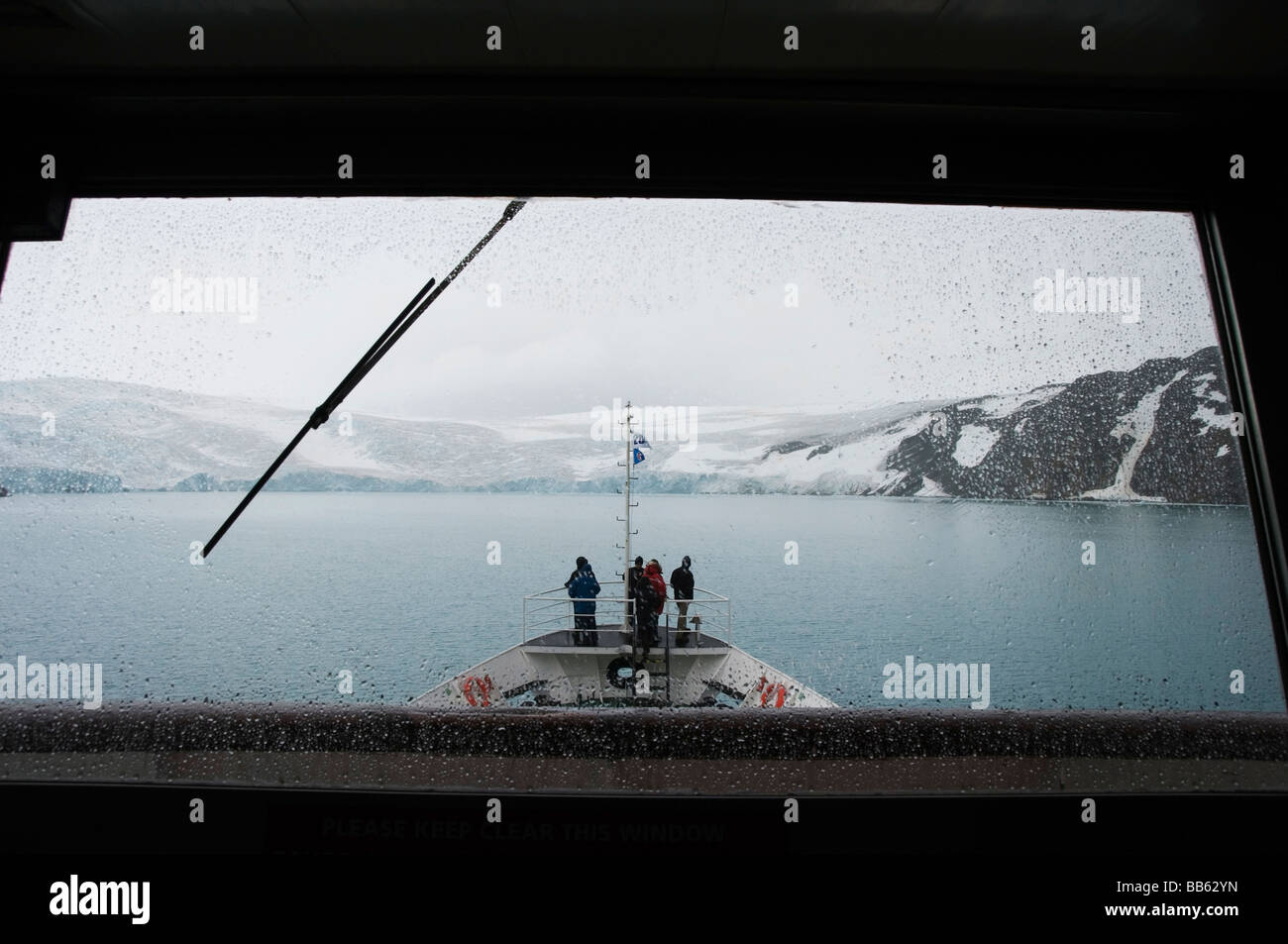 Team members on an expedition ship as it approaches King George Island off the Antarctic Peninsula - Stock Image