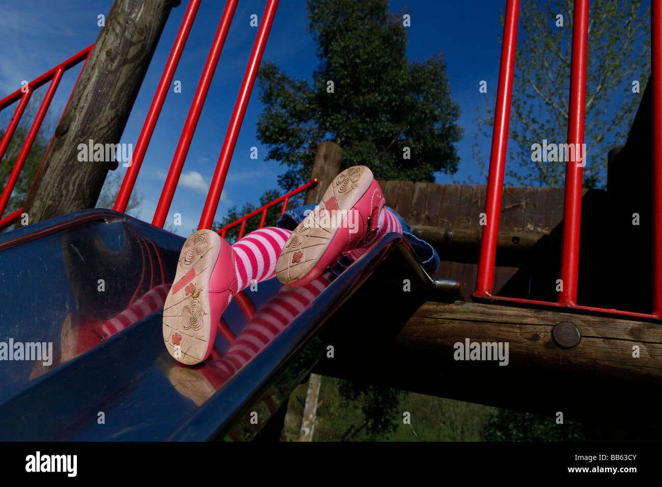 Little girls feet appearing at the top of the slide in the park on a sunny day. - Stock Image
