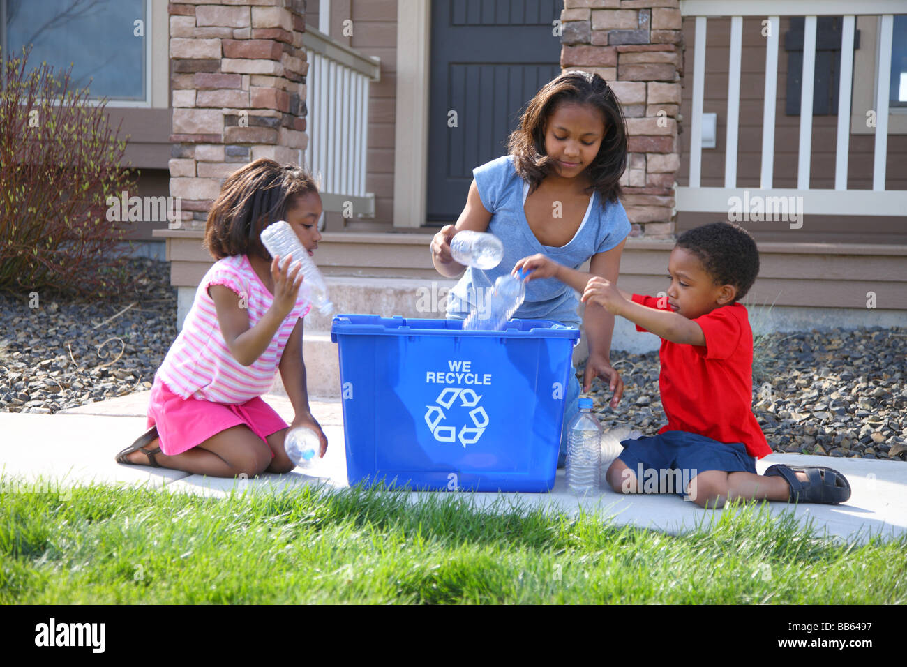Three children putting items into recycle bin - Stock Image
