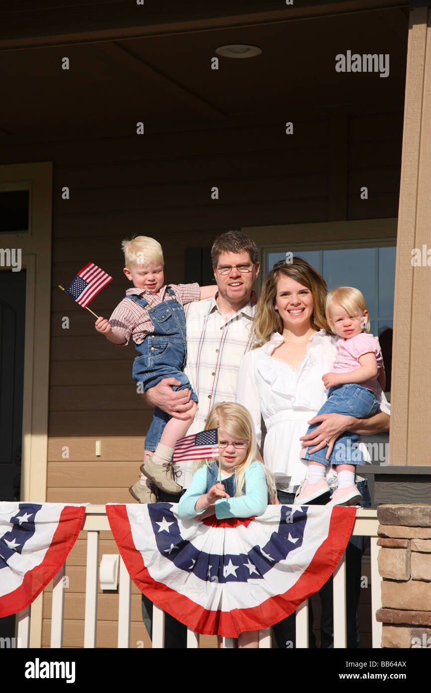 Patriotic family on front porch with children waving flags - Stock Image