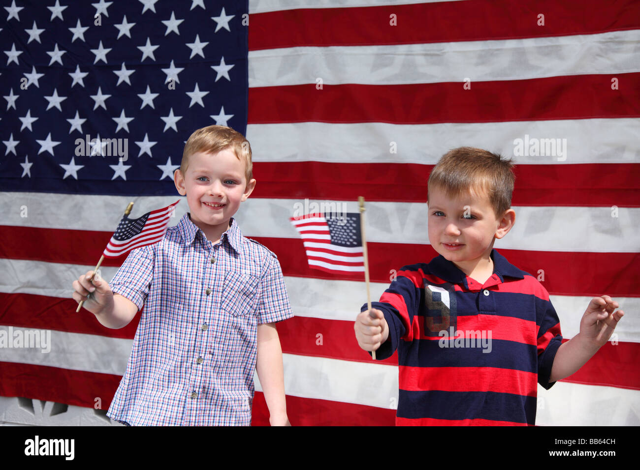 Two young boys waving American Flags - Stock Image