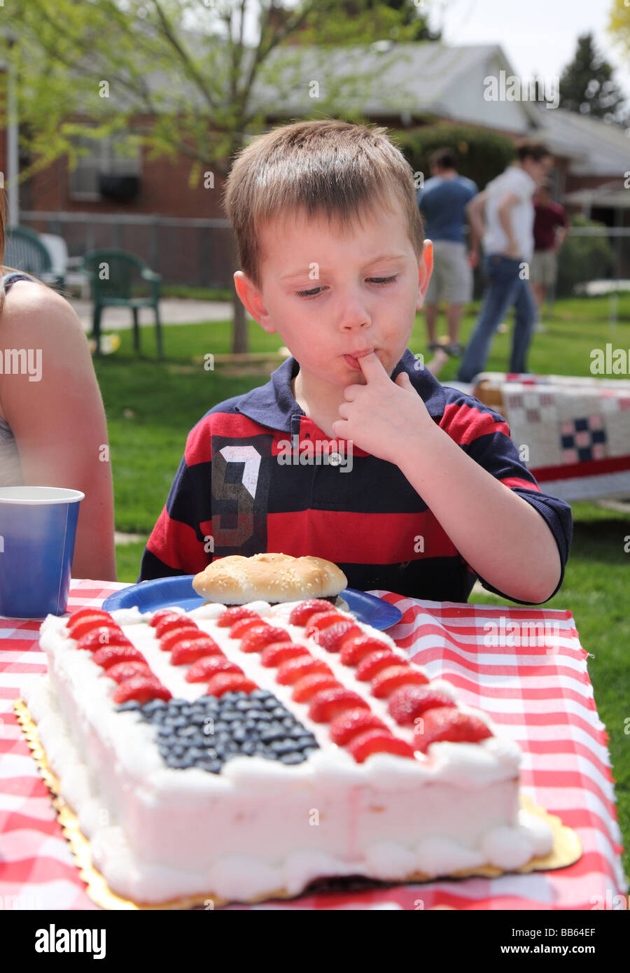 Young boy eating frosting off patriotic cake - Stock Image