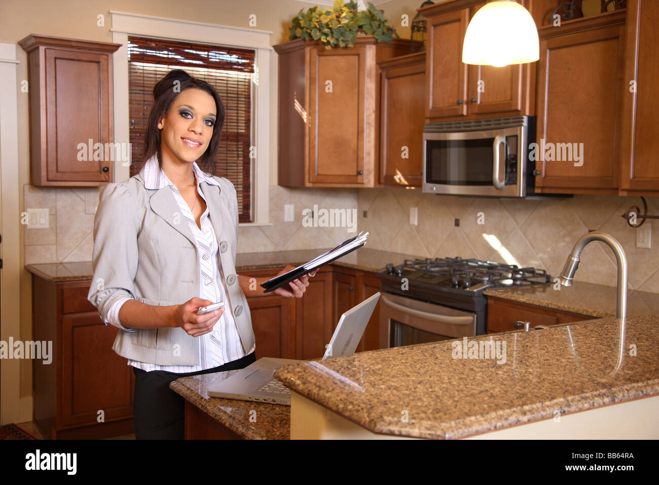 Realtor with paperwork laptop and cell phone in kitchen - Stock Image