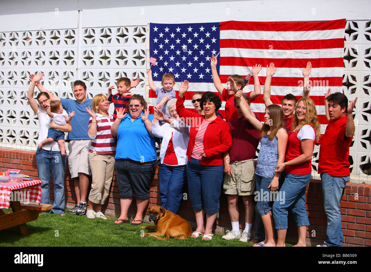 Large group of people in front of American flag waving hands - Stock Image
