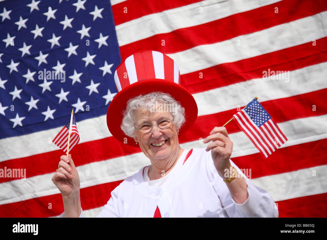 Patriotic senior woman waving flags and smiling - Stock Image