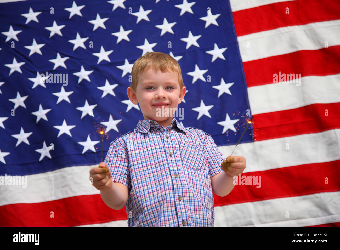 Young boy waving sparklers in front of American flag Stock Photo