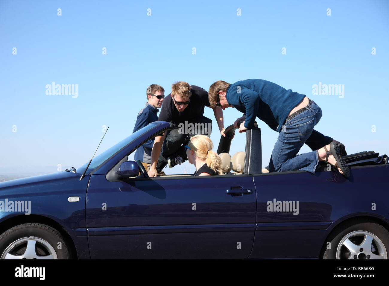 Group of young people getting into convertible car - Stock Image