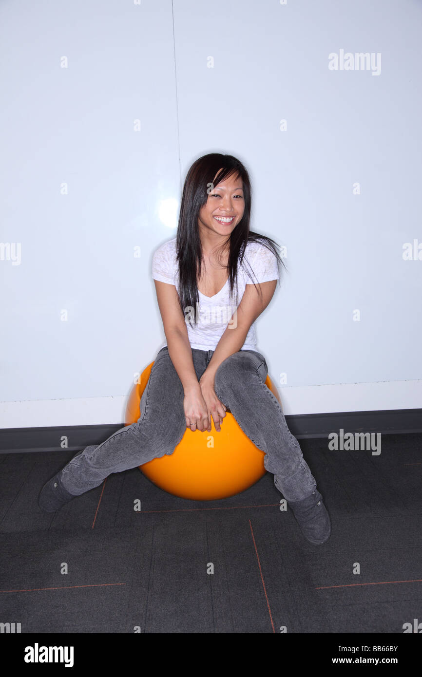 Asian woman sitting on orange ball smiles - Stock Image