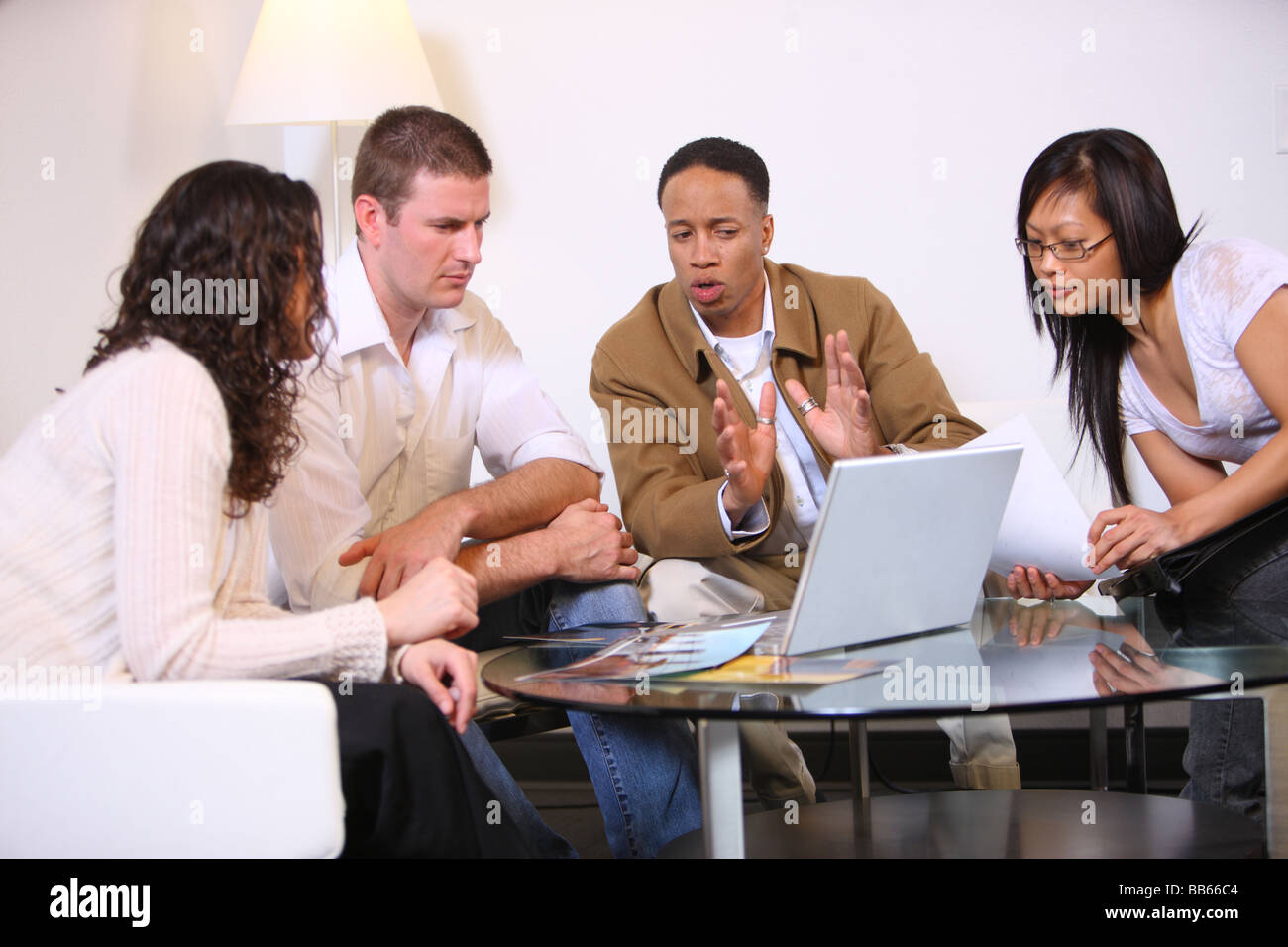 Group of young businesspeople brainstorming together with laptop - Stock Image