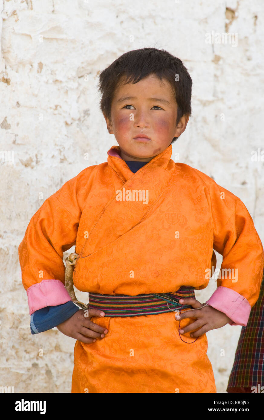 Young Boy wearing orange 'gho' at tsechu or festival, Ura, Bumthang Valley, BHUTAN - Stock Image