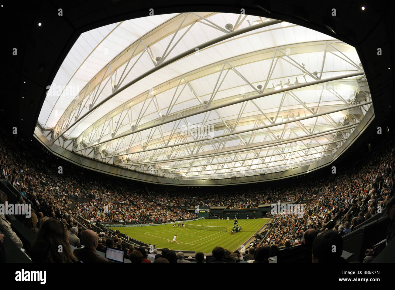 View of play on Centre Court under the new retractable roof during the Wimbledon Centre Court Celebration event. - Stock Image