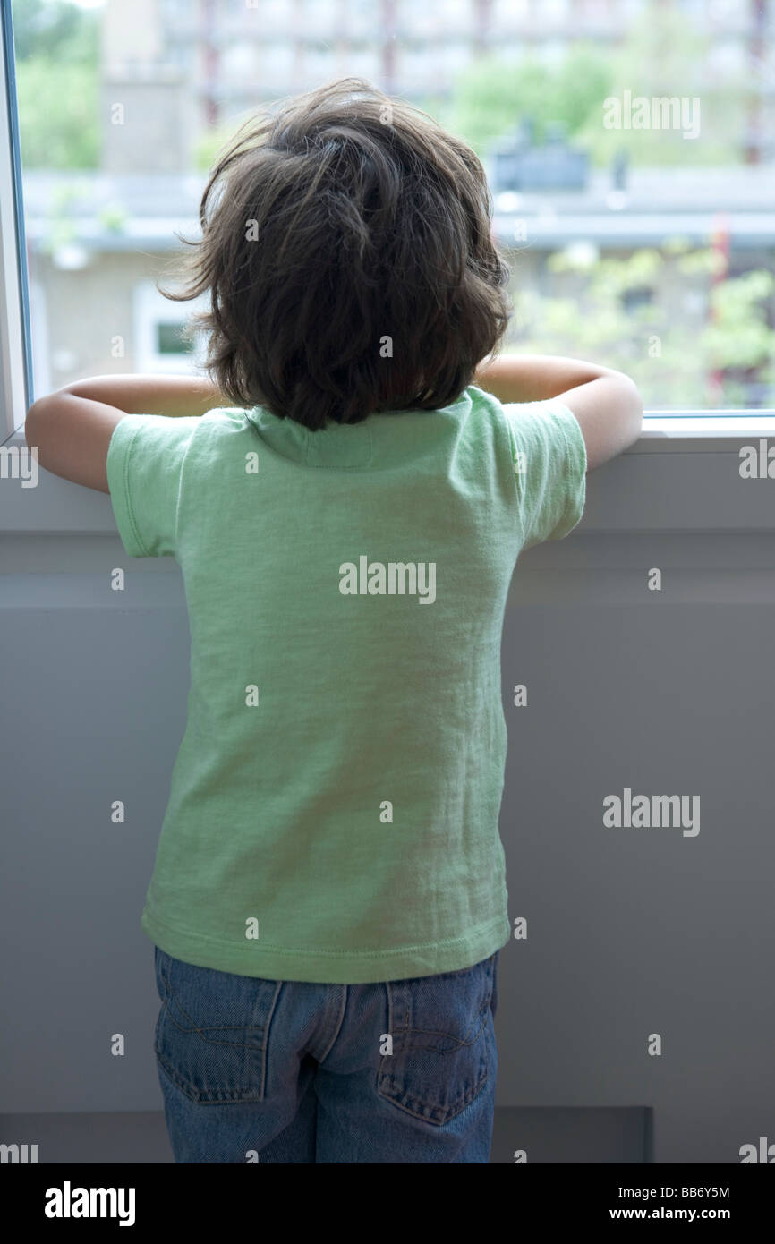 Backview of a lonely little boy looking out of the window - Stock Image