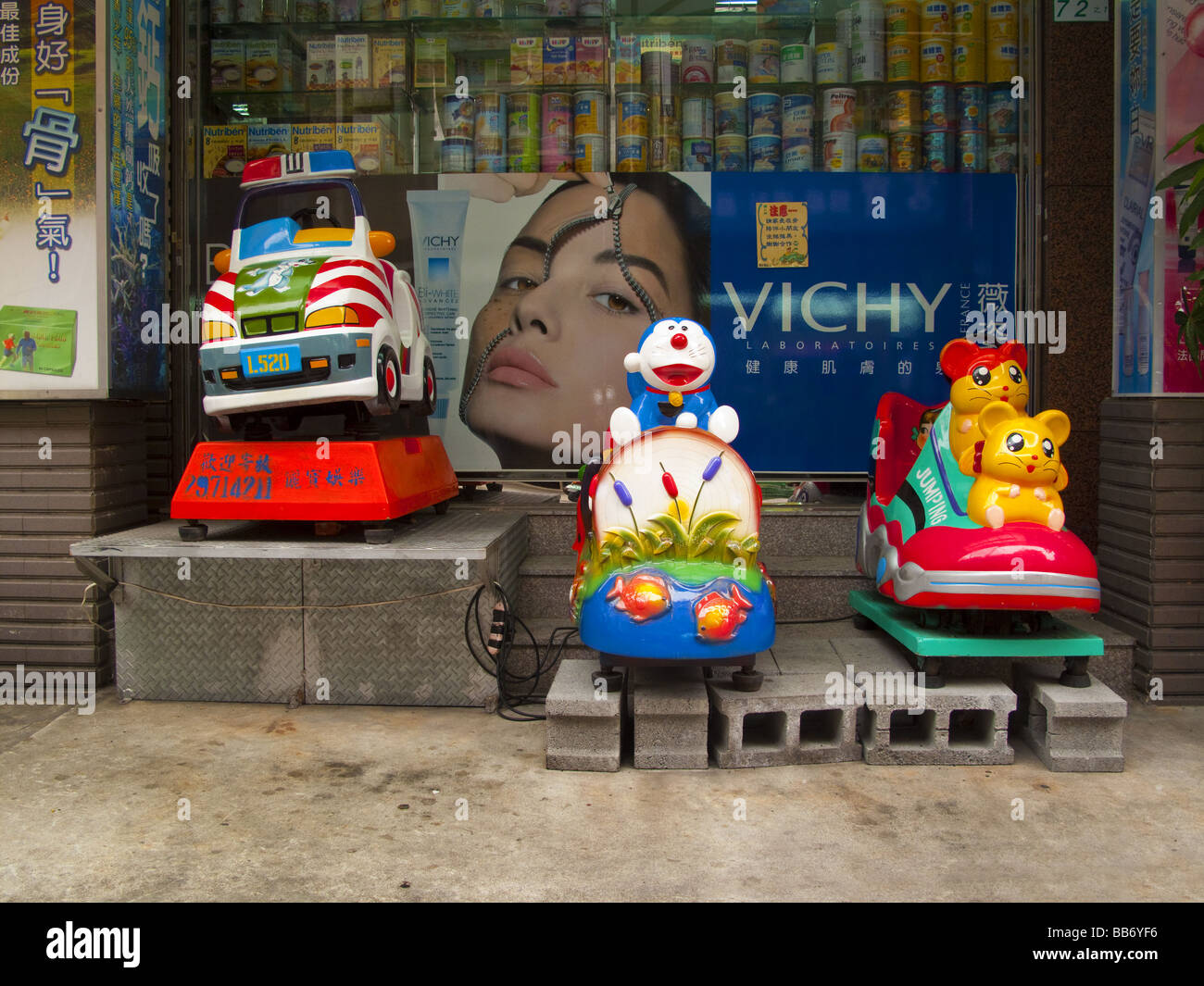 Childrens rides outside a chemist Taipei, Taiwan - Stock Image