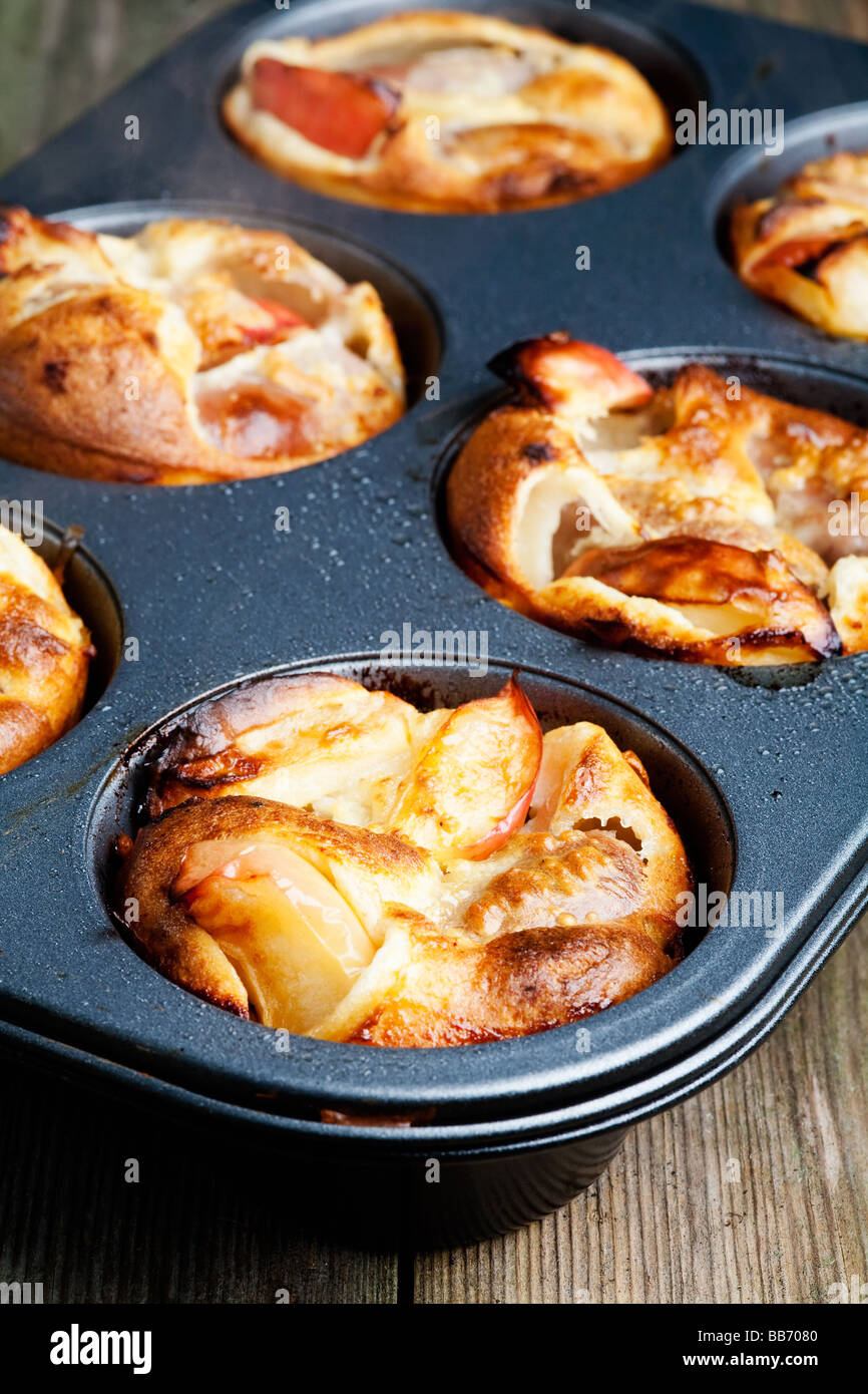 Individually cooked Toad in the Hole with apples A traditional English dish of sausages cooked in Yorkshire pudding - Stock Image