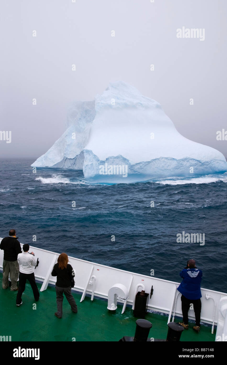 Tourists looking at an iceberg from the deck of a cruise ship in the Southern Ocean near Antarctica - Stock Image