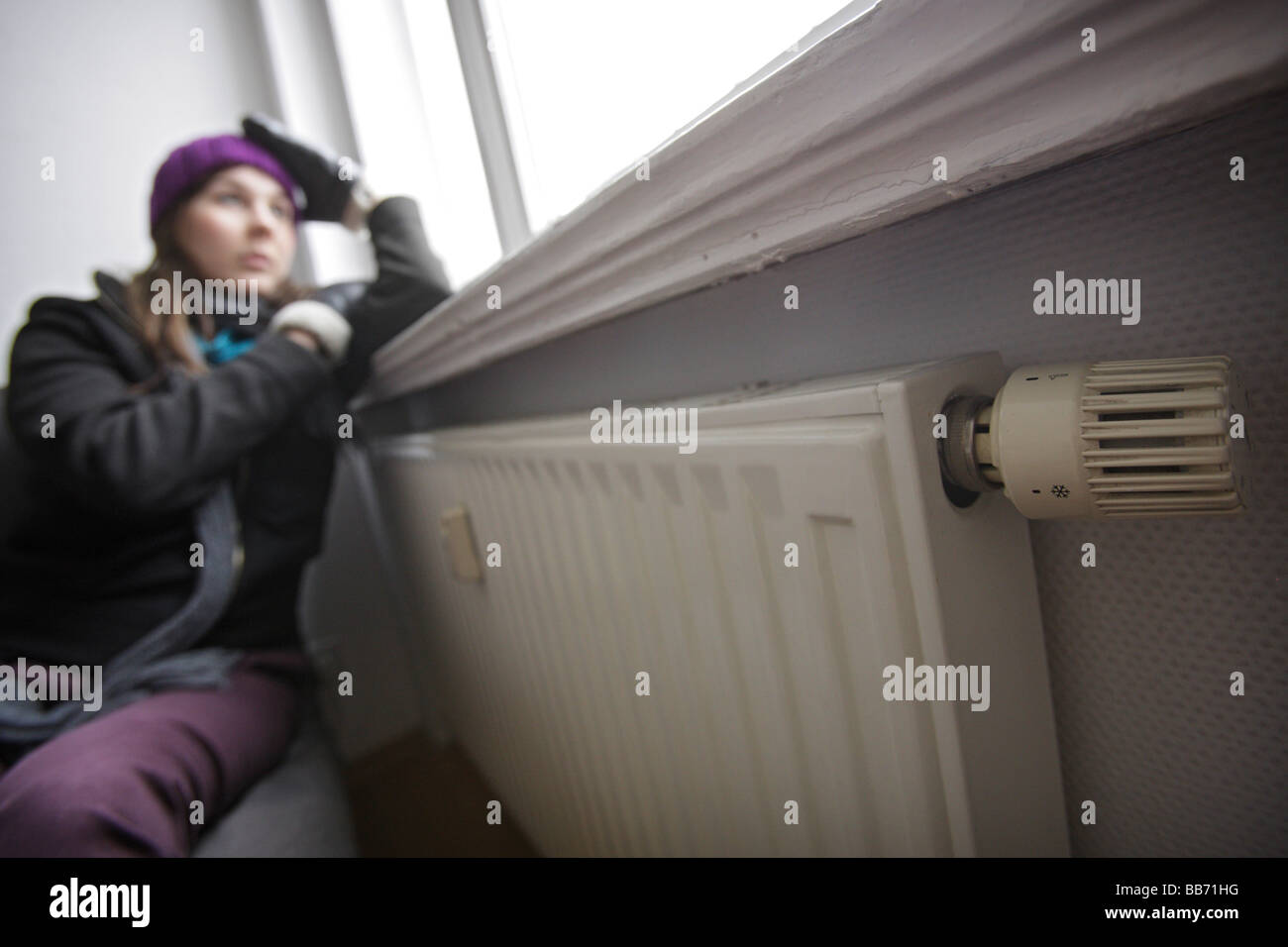 Saving heating coasts young woman at home wearing a cap and gloves - Stock Image