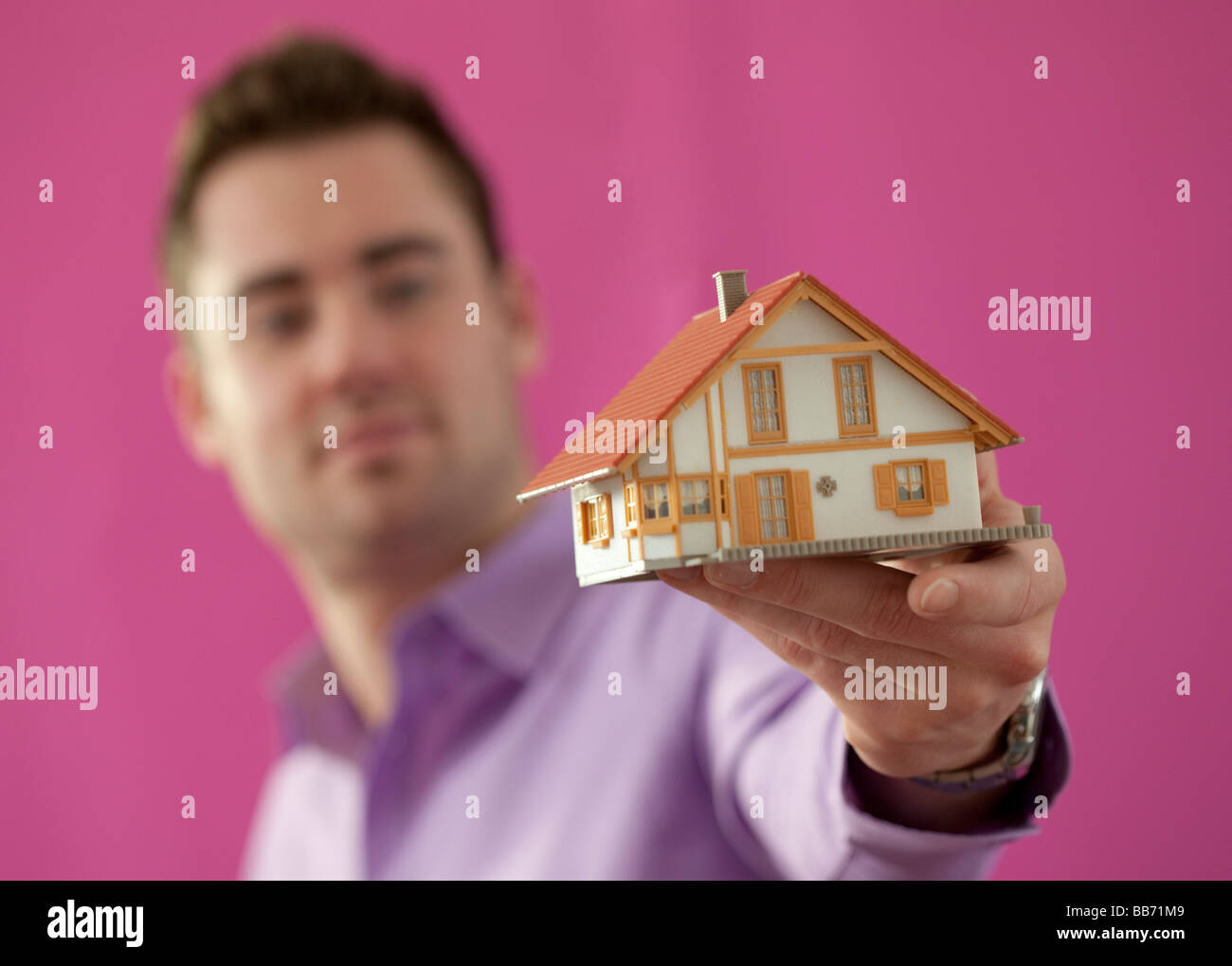 Young man holding a little house - Stock Image