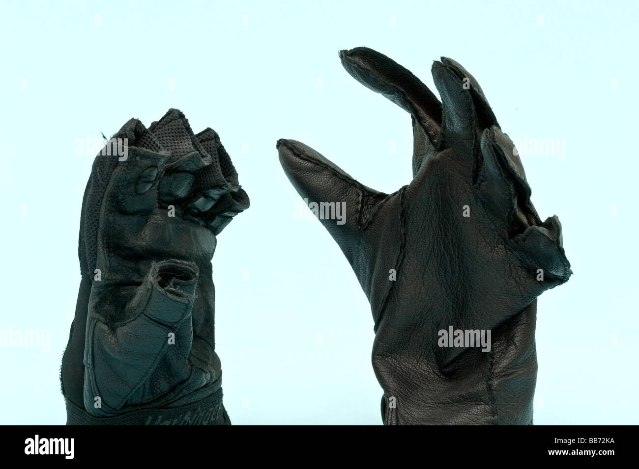 Two gloves, one expensive leather, and another a exercise glove - Stock Image