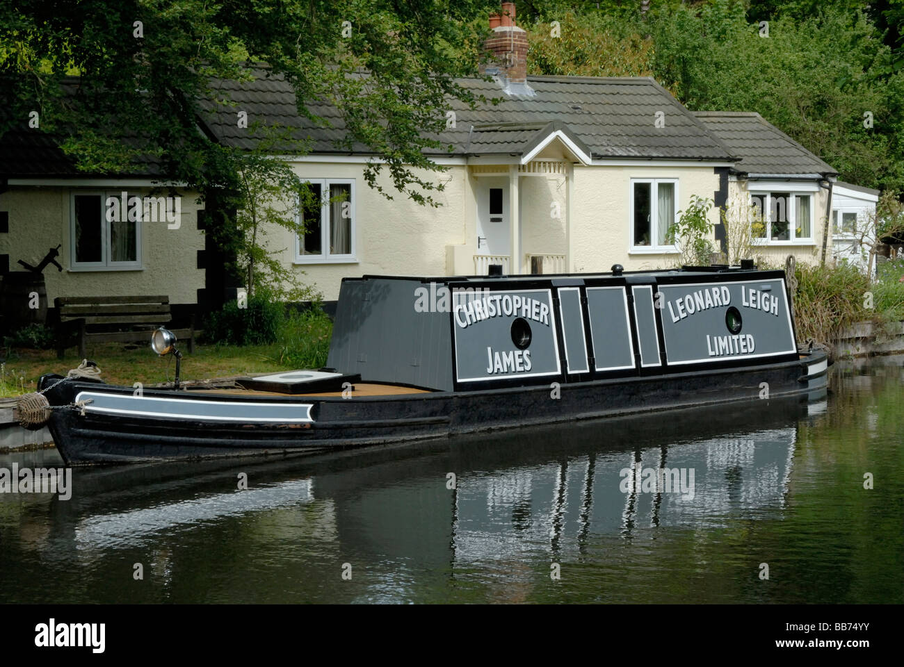 Narrow beam motor tug moored before a lock cottage, Deepcut, Basingstoke Canal, Surrey, England - Stock Image