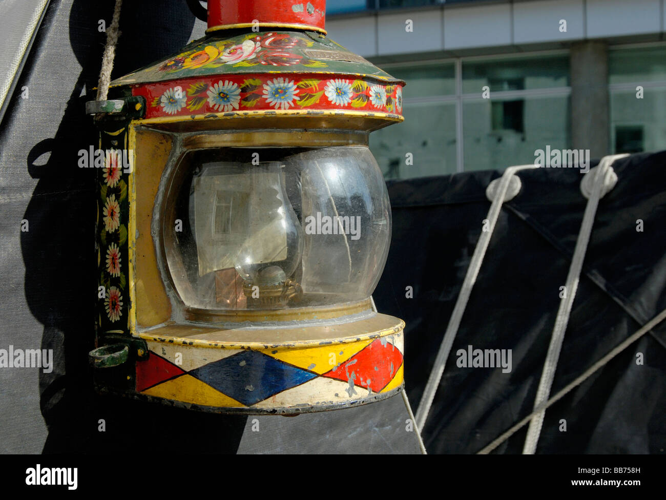 Traditional paraffin tunnel lamp painted with flowers and diamonds on cratch board of a working narrowboat, London, - Stock Image