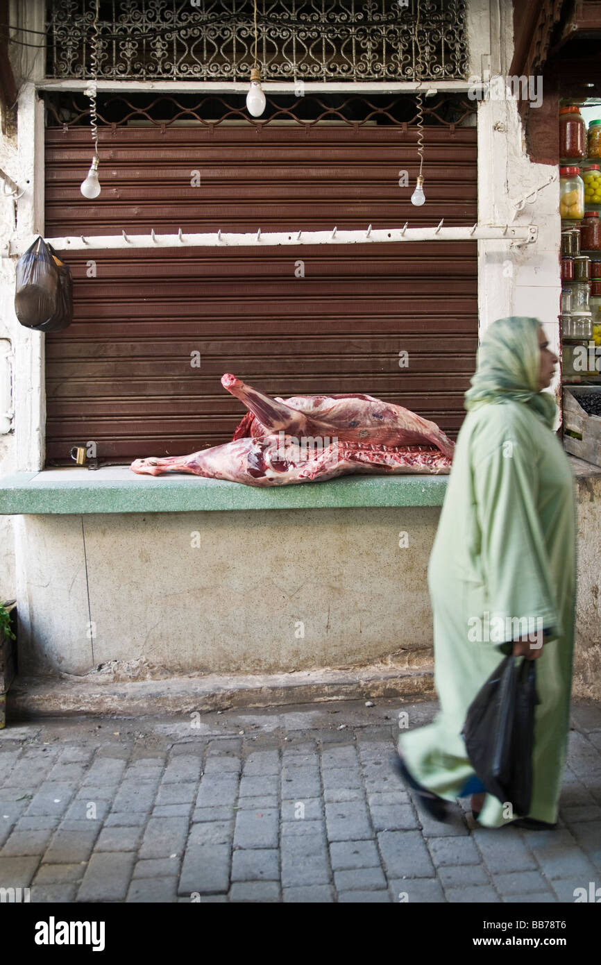 Woman walking past closed butcher's shop with carcass left out on the counter to the elements. Not wrapped up, - Stock Image