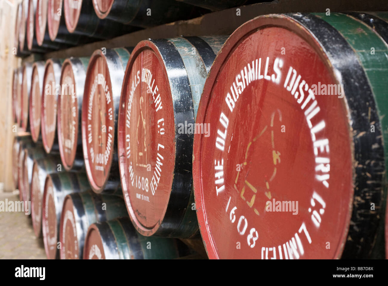 Whiskey Barrels. Brightly painted whiskey aging barrels decorate the old distillery at Bushmills. - Stock Image