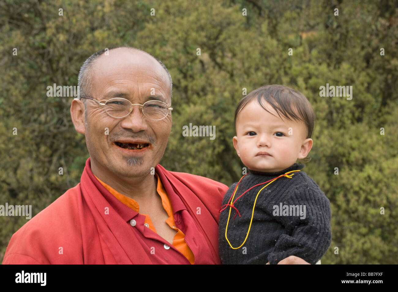 Man eating betel nut, with grandchild, BHUTAN - Stock Image