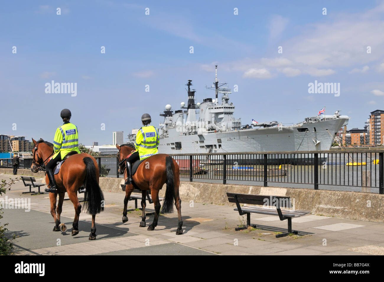 Royal Navy warship HMS Illustrious light aircraft carrier moored in River Thames Greenwich London passing mounted - Stock Image