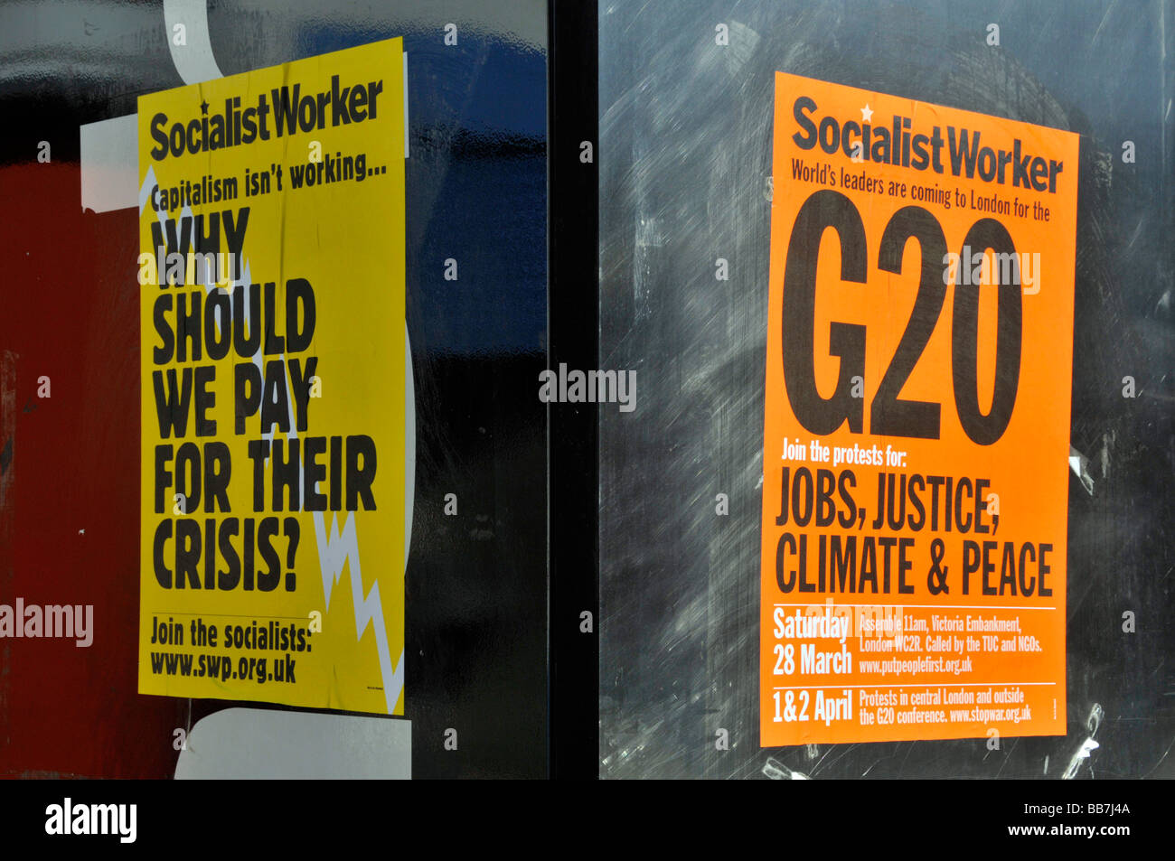 Socialist Worker posters stuck on side of phone box during the G20 summit in London - Stock Image