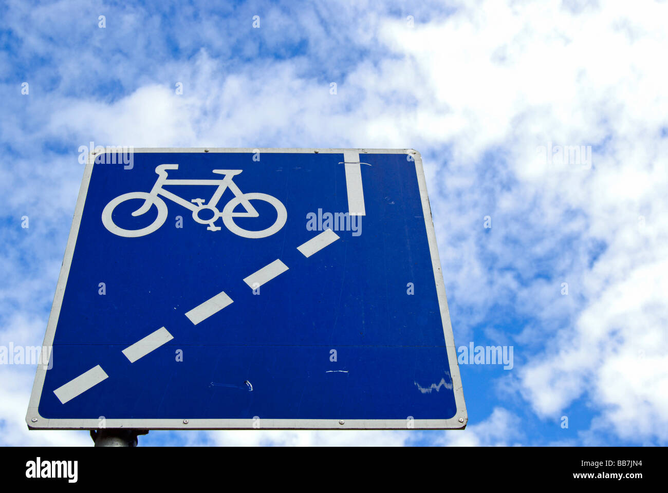 seen under a mottled sky of patch work cirrocumulus cloud british blue and white road sign indicating mandatory - Stock Image