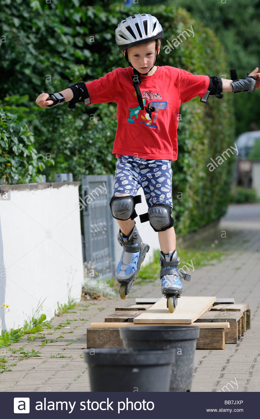 Boy, age 7, Inlineskates, ride over obstacle - Stock Image