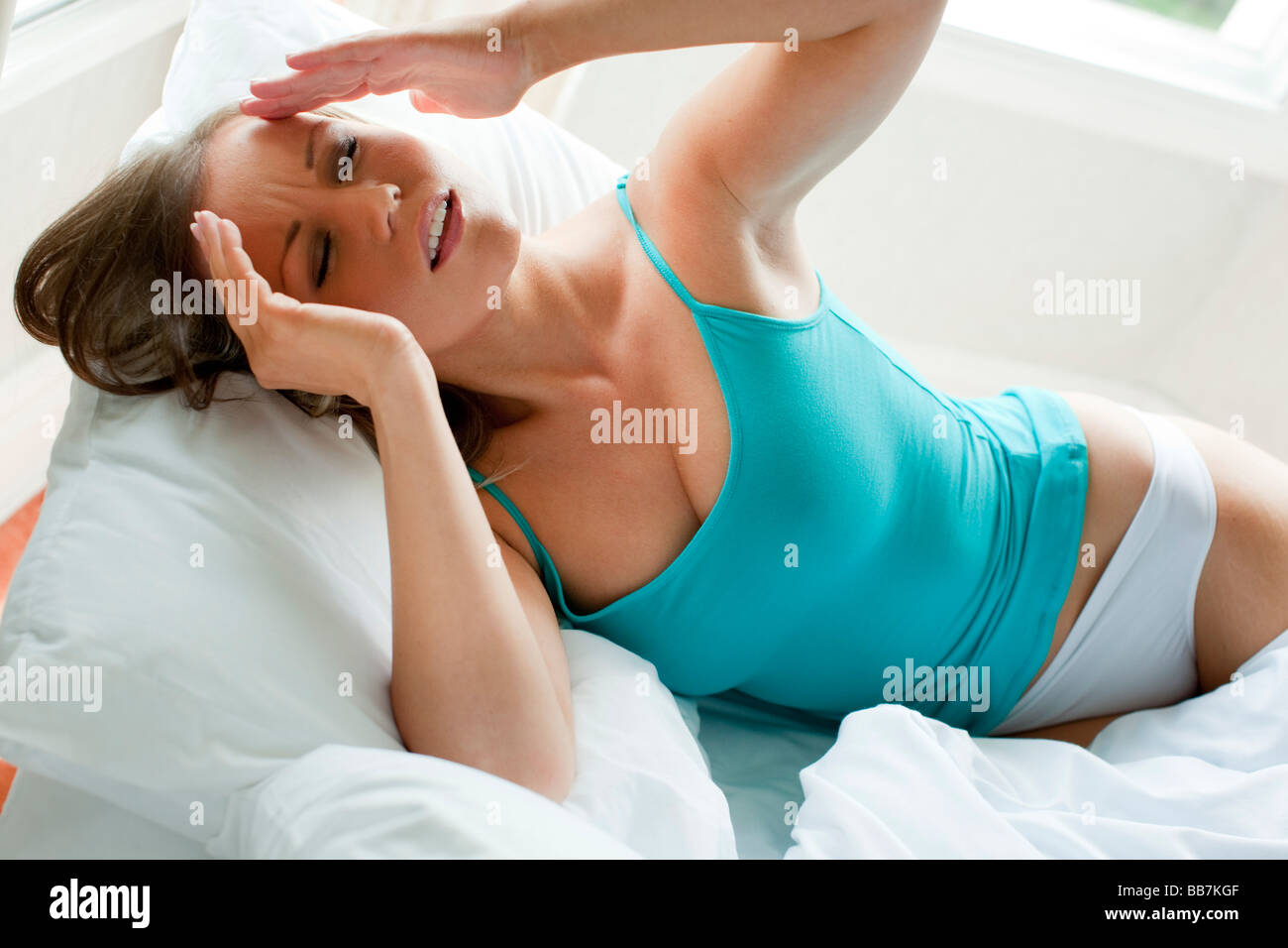 Girl in bed with headache - Stock Image
