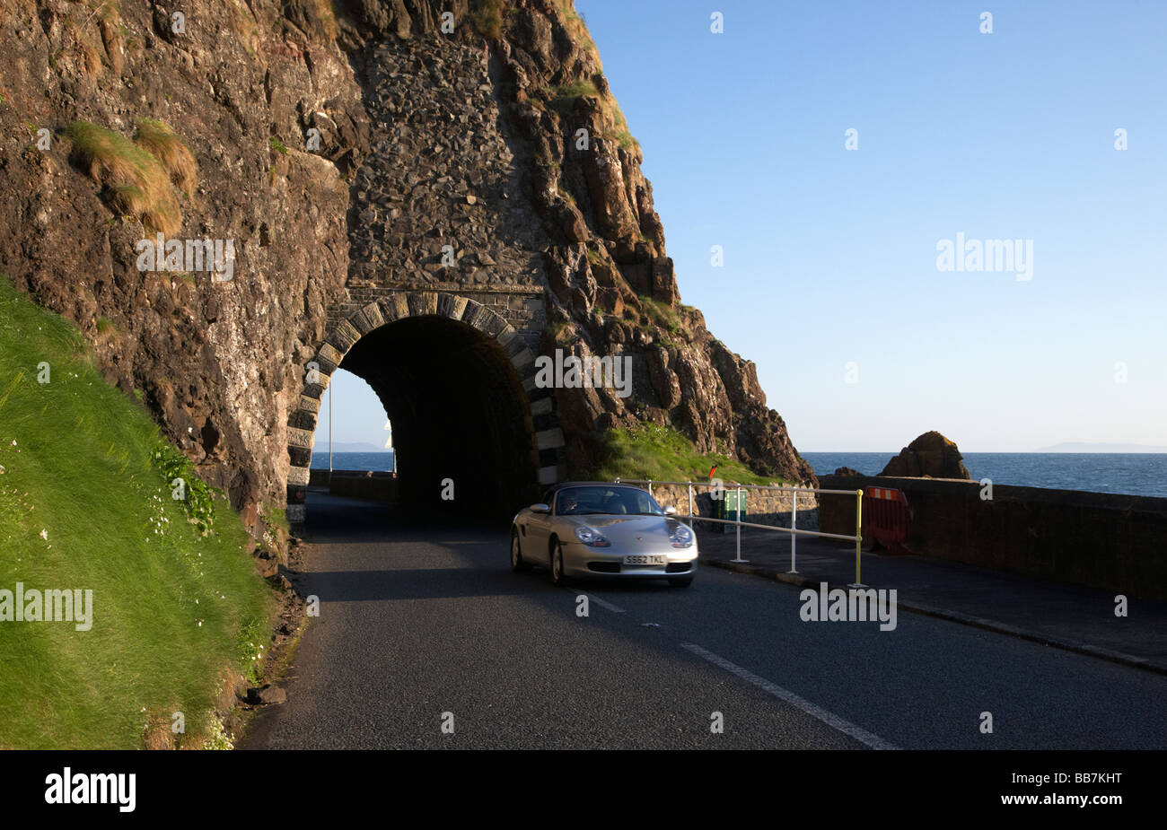 porsche car on the the A2 causeway coastal route coast road passes through the black arch outside Larne Stock Photo