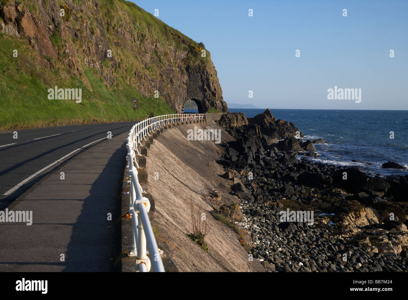 The A2 causeway coastal route coast road and pathway passes through the black arch outside Larne - Stock Image
