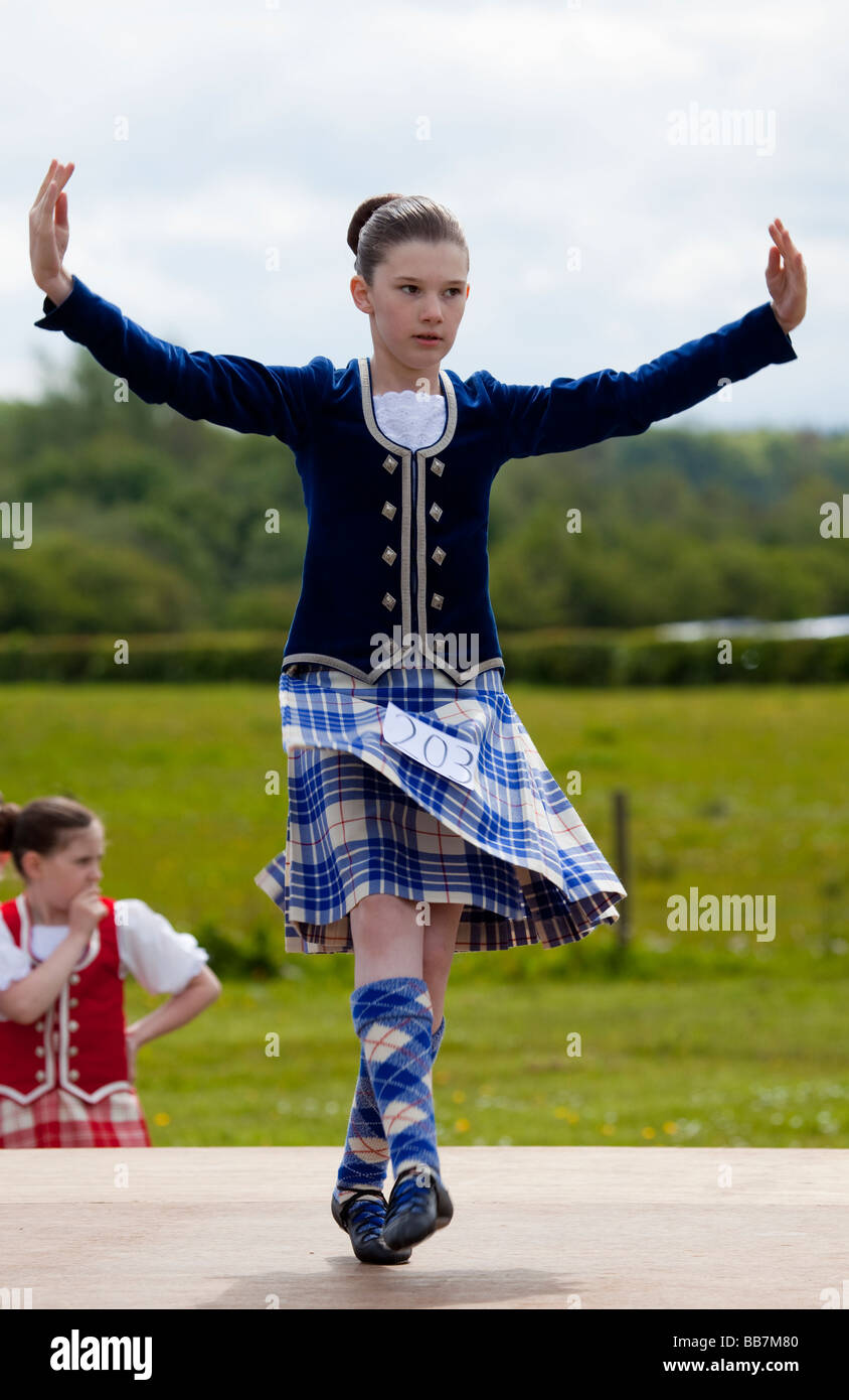 Female Highland Dancer dancing in a competition on an outdoor stage. Stock Photo