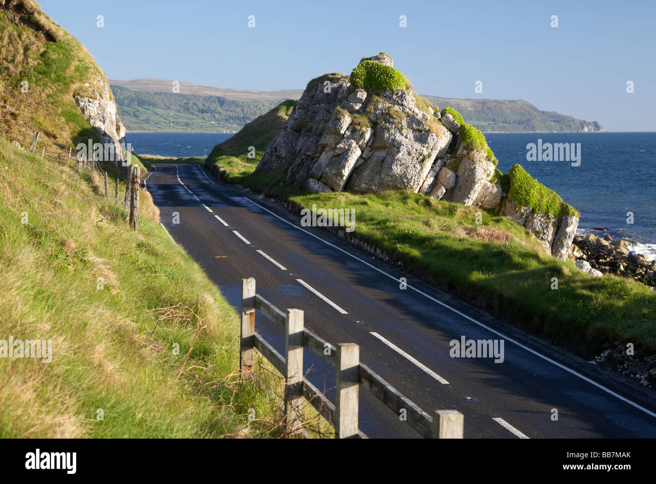 The A2 causeway coastal route coast road passes through limestone rock formations County Antrim Northern Ireland - Stock Image
