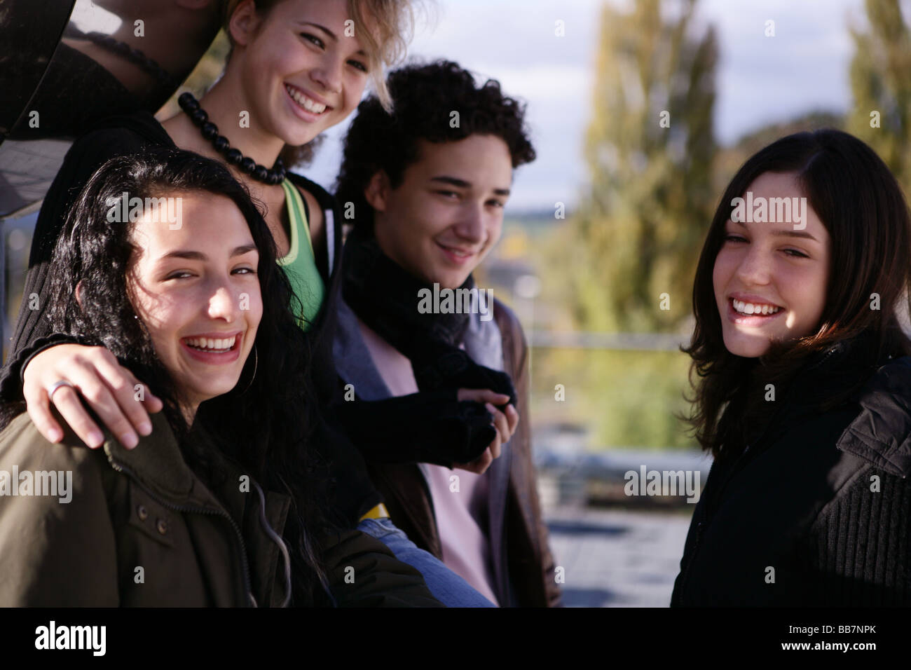 Portrait of teenager group smiling outside - Stock Image