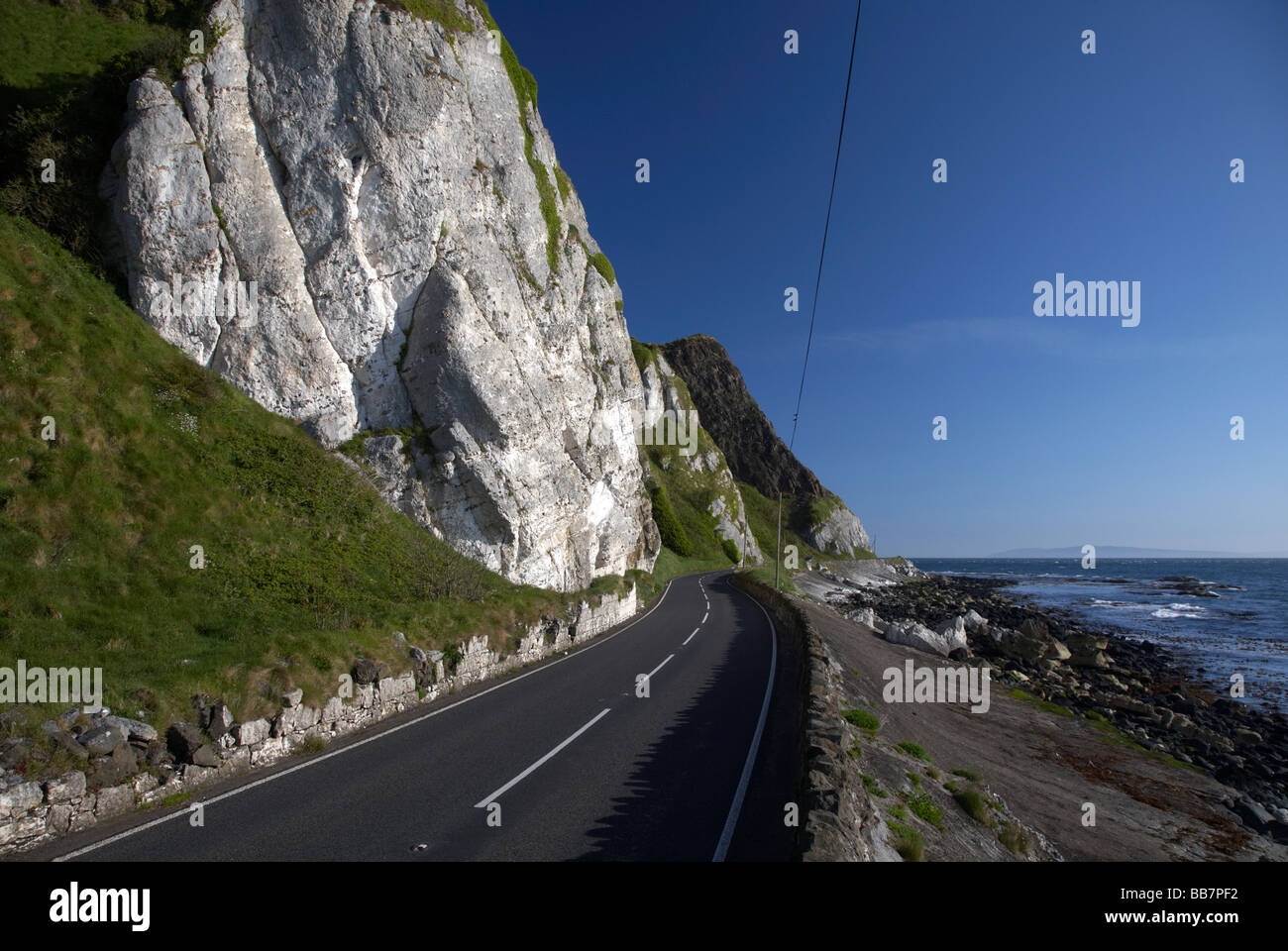 The A2 causeway coastal route coast road at Garron Point under Limestone and basalt cliffs County Antrim Northern - Stock Image
