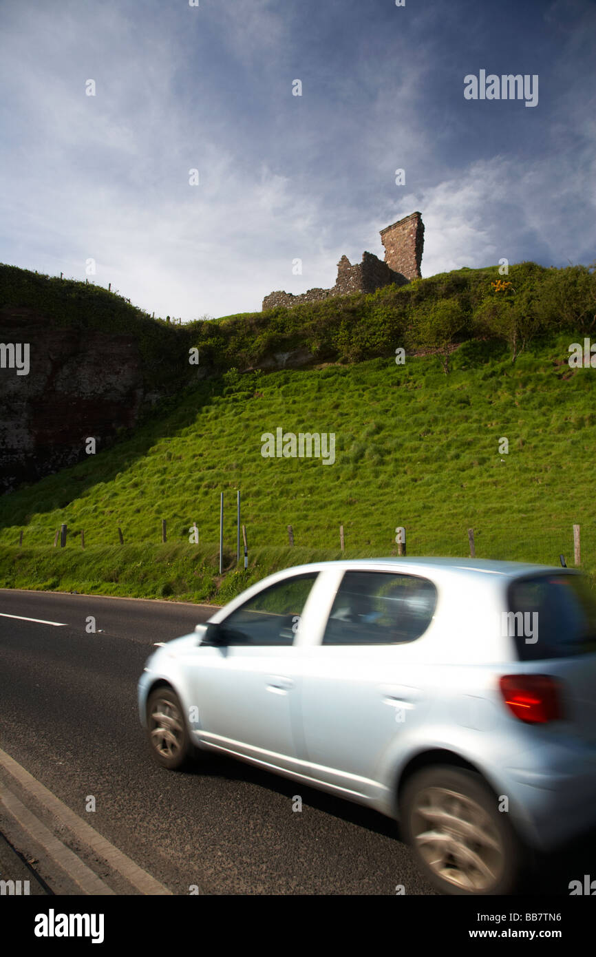car touring the antrim coast beneath red bay castle on the A2 causeway coastal route coast road County Antrim Stock Photo