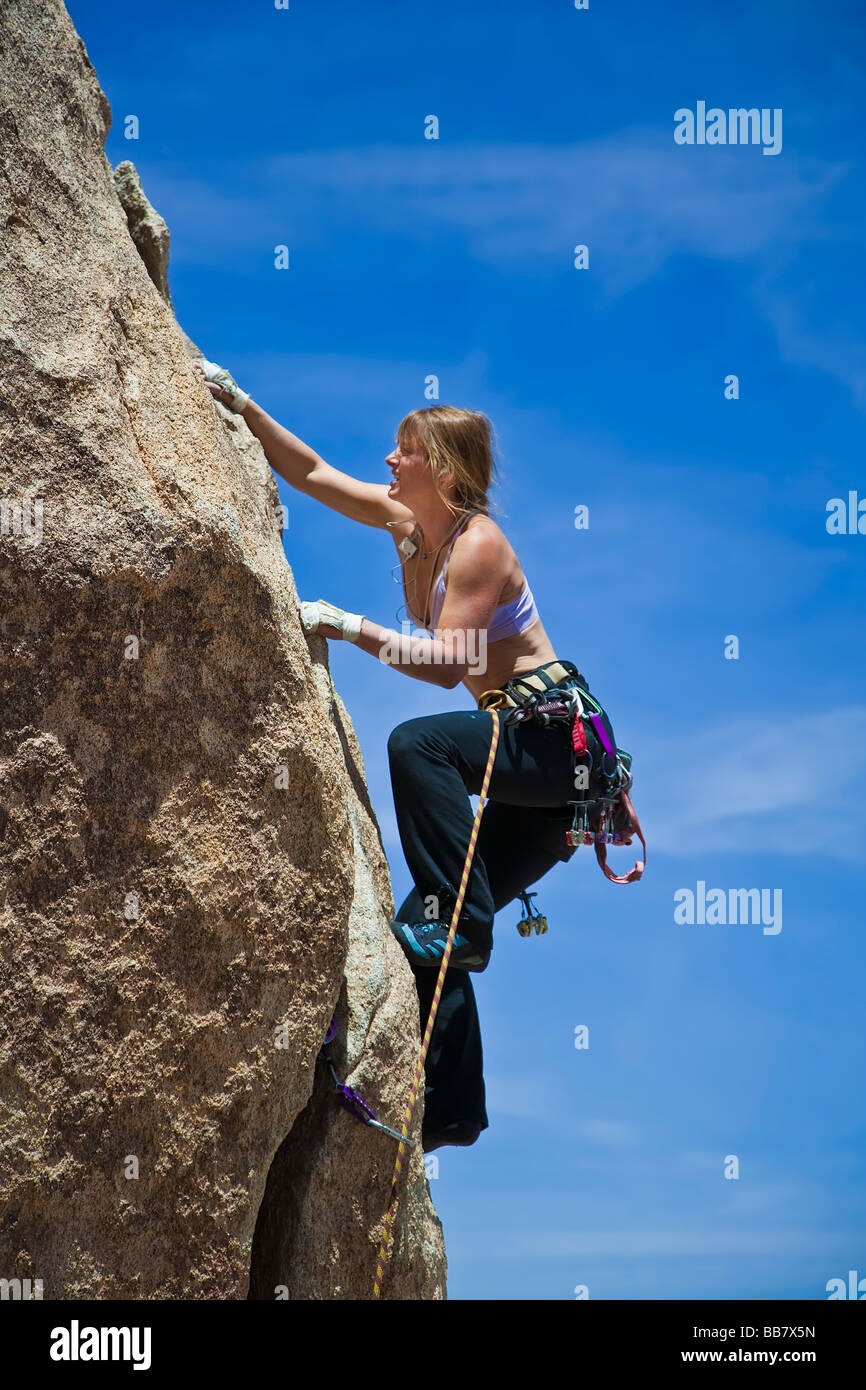 Female rock climber is focused on the next move Stock Photo