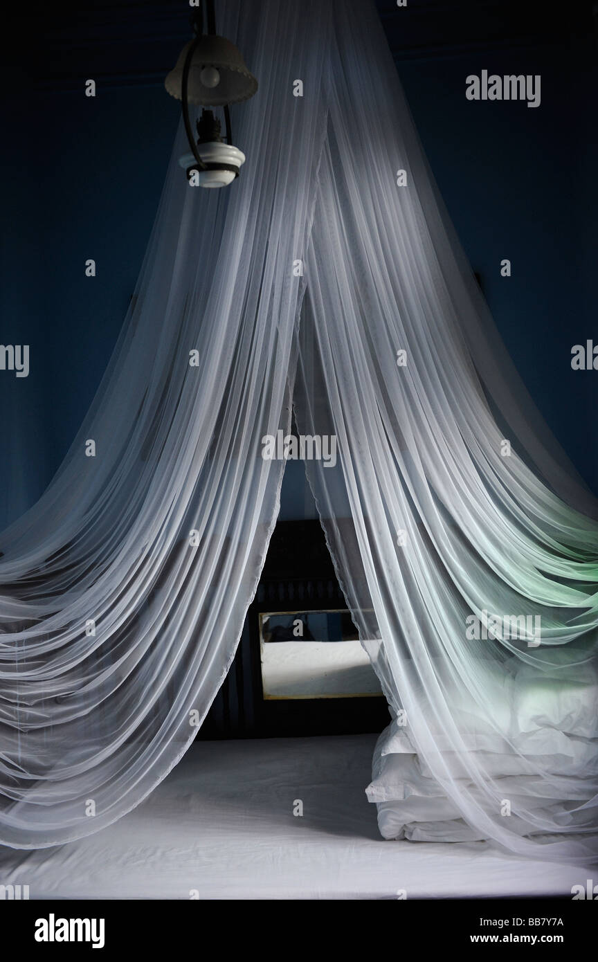 White mosquito net above the bed in a hotel. - Stock Image
