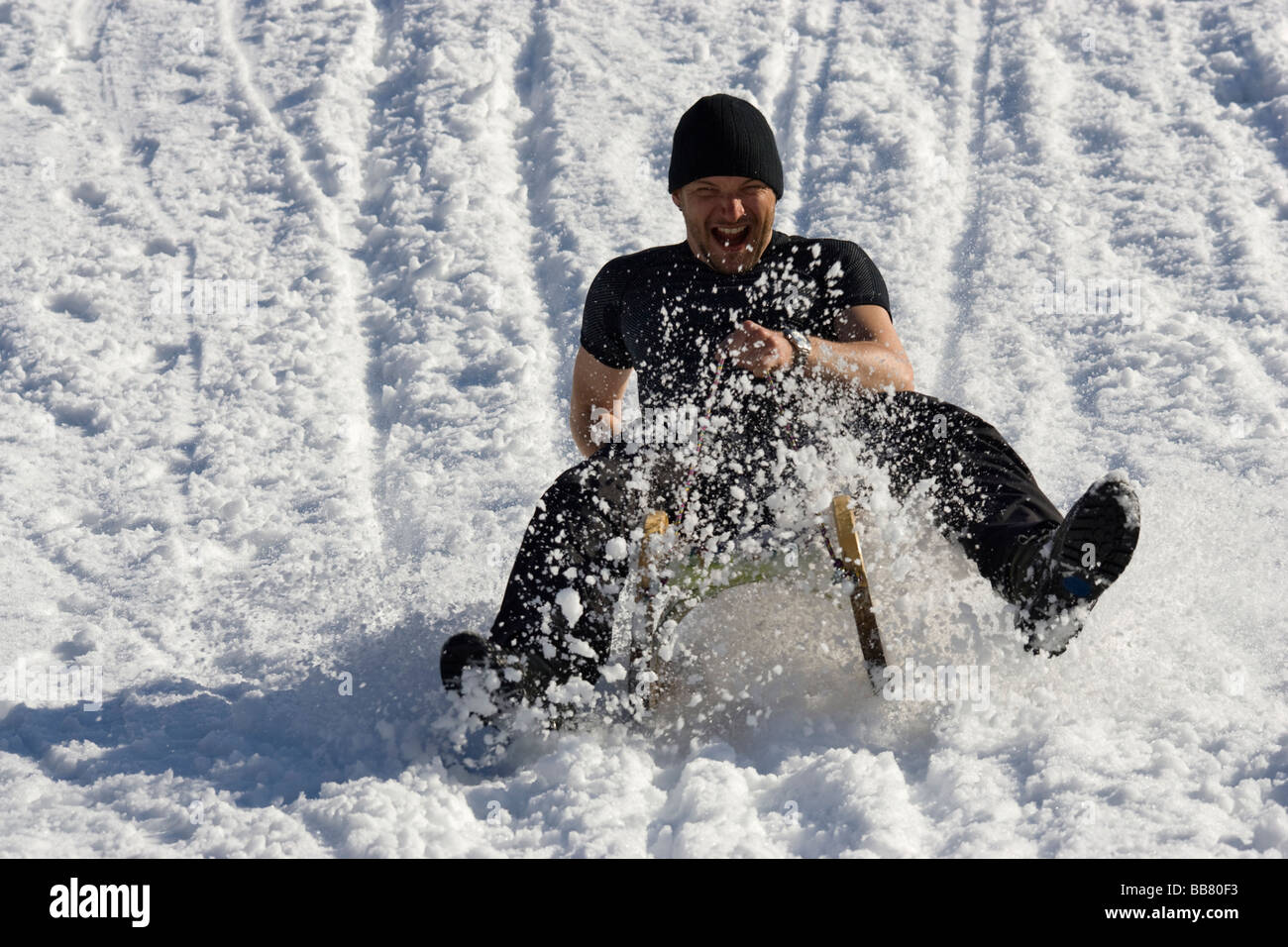 Man sledging down a hill, wearing a t-shirt, Zillertal, Austria - Stock Image