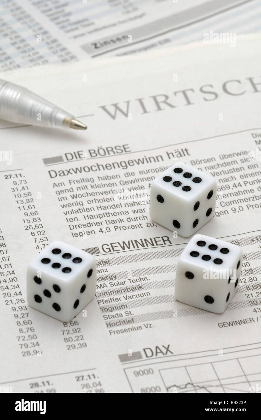 Dice on the business section of a newspaper, stock exchange, symbolic picture for business - Stock Image