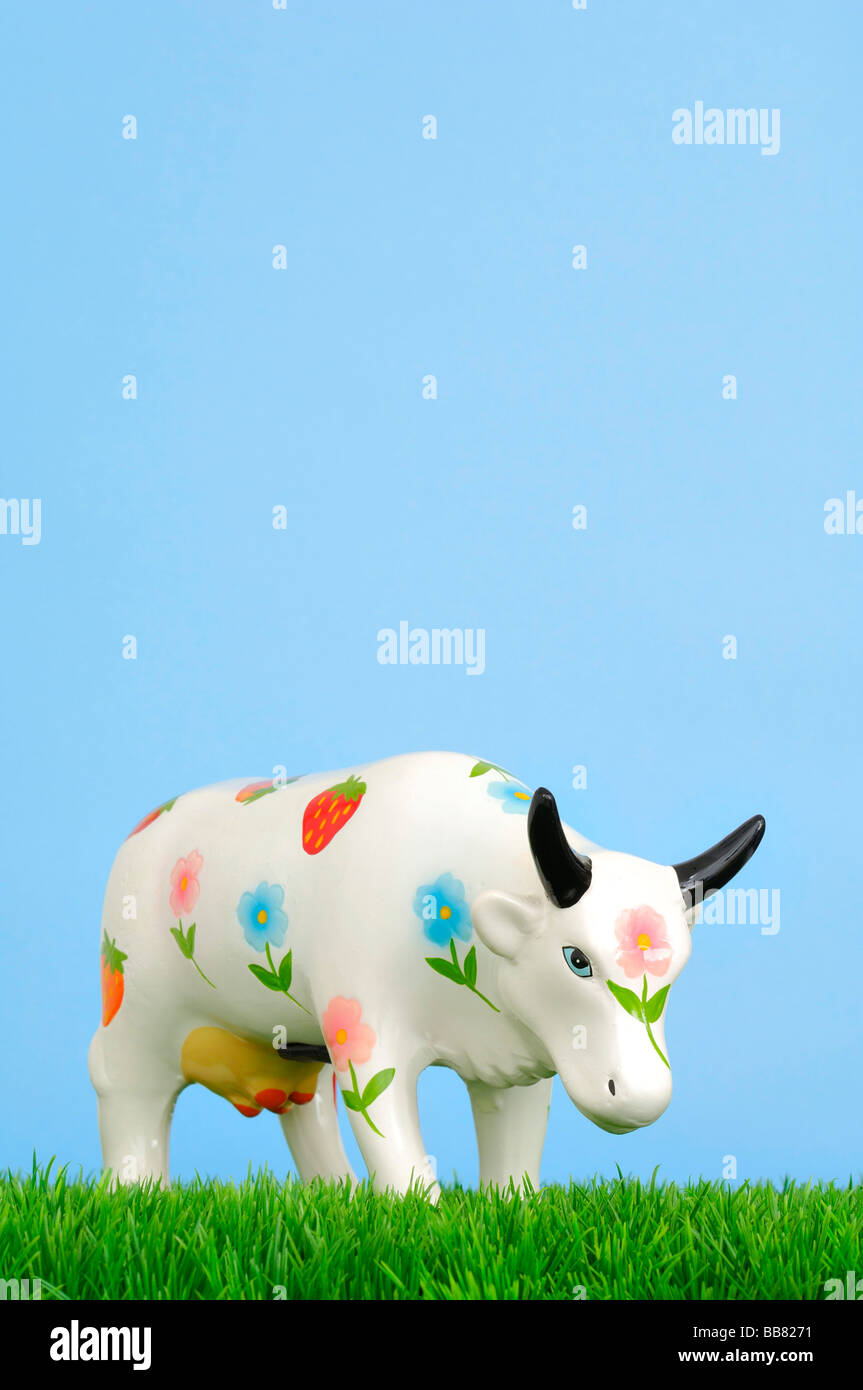 Ceramic cow with blossoms, piggy bank on grass - Stock Image