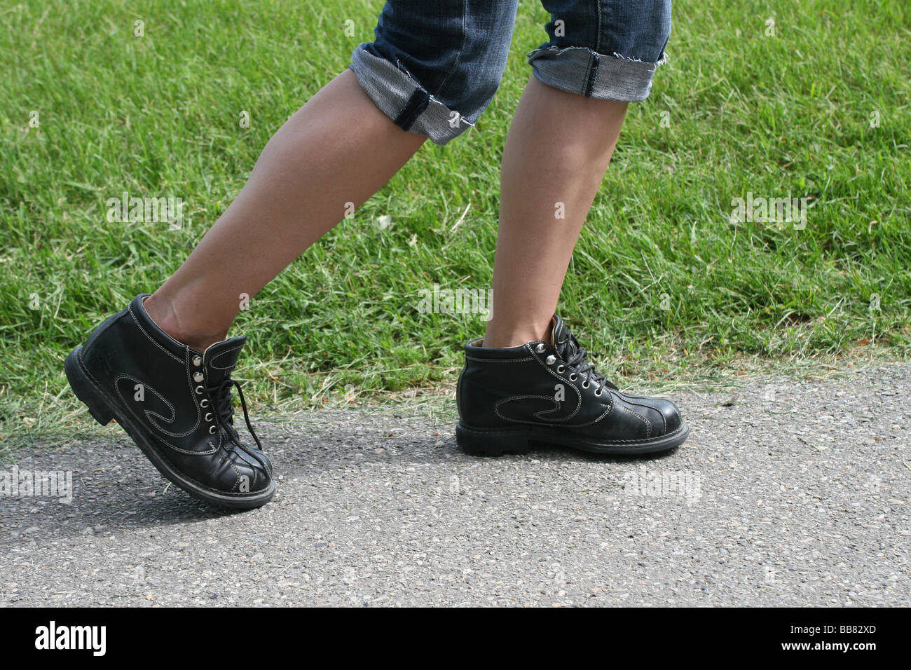 female hiker wearing jeans and and hiking boots walking on a paved pathway - Stock Image