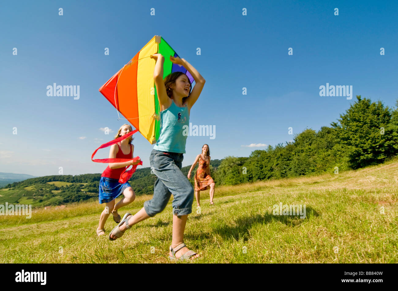 Teenagers running with a kite over a meadow - Stock Image