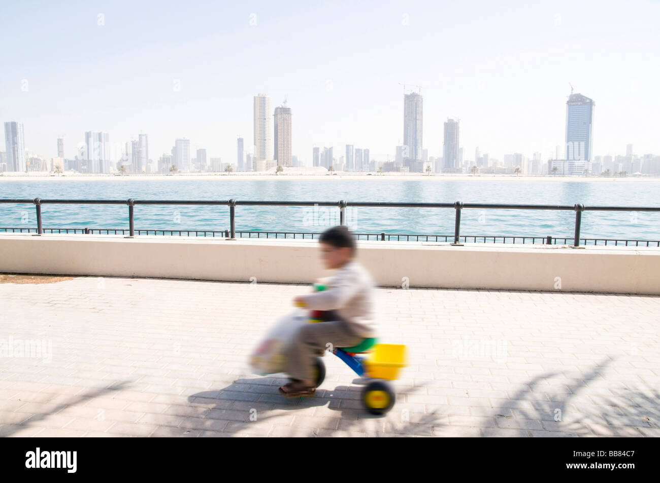 Child on tricyle in front of high rises with motion blur, Dubai, United Arab Emirates - Stock Image