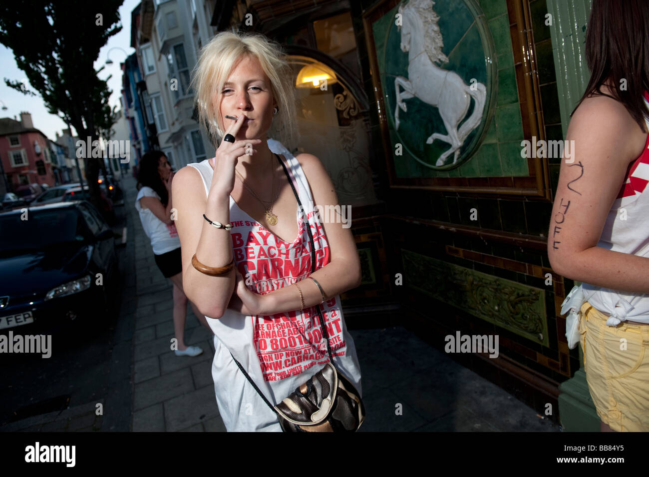 Young blonde haired woman smoking cigarette outside on a Carnage organised pub crawl, Aberystwyth Wales UK - Stock Image